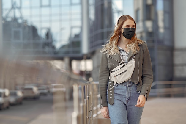 Woman in a mask stands on the street