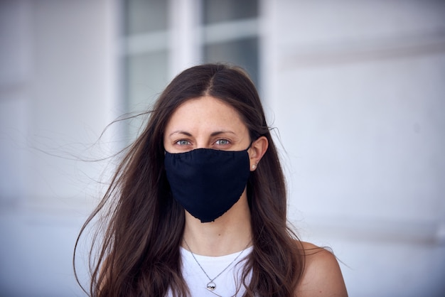 Woman in mask on street due to epidemic of coronavirus in city. protection against virus and infection