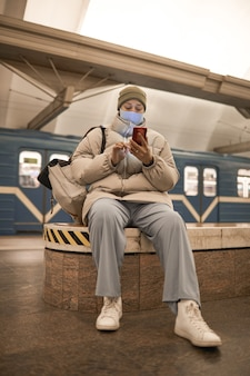 Woman in mask typing a message on her mobile phone while sitting in subway
