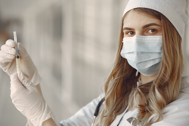 Woman in a mask and uniform holding a syringe in her hands