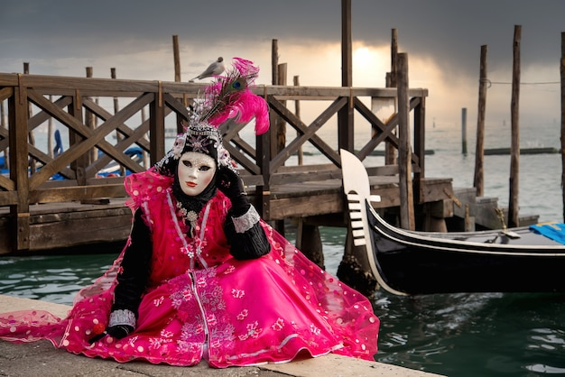 Woman in mask wearing ornate colorful pink carnival costume sits at san marco lagoon with floating gondolas at sunset.  carnival in venice, italy