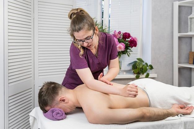 Массажист женщина делает массаж молодому человеку. оздоровительная процедура. профессиональный массаж спины в спа-салоне.
