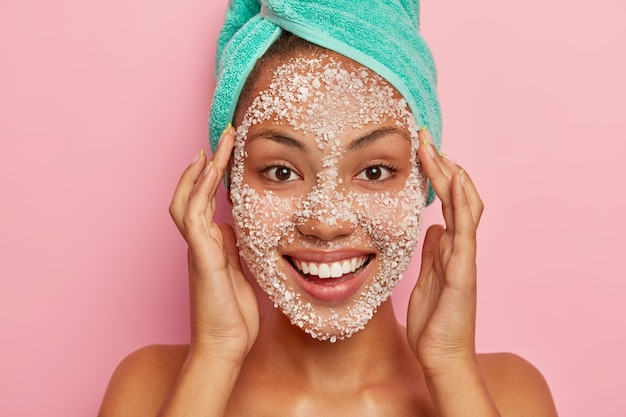 Woman massages face, applies natural scrub mask, cleans facial skin for having young look, has manicure, wears wrapped towel on head, isolated on pink wall