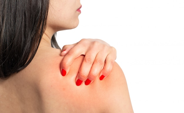 The woman massages the shoulder with her hand. the view from the back