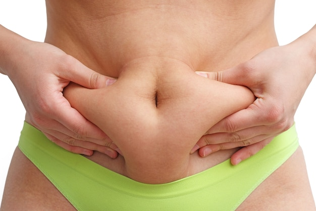 A woman massages the skin on her stomach with her hands. excess weight, cellulite.