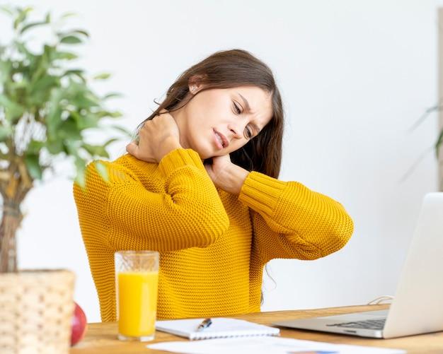 コンピューターで長時間働くことで首の痛みをマッサージする女性