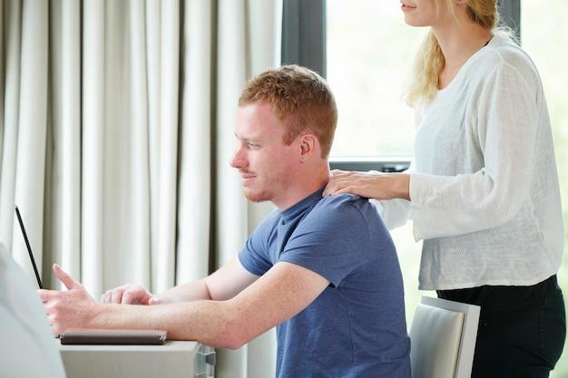 일하는 남자 친구에게 어깨를 마사지하는 여자