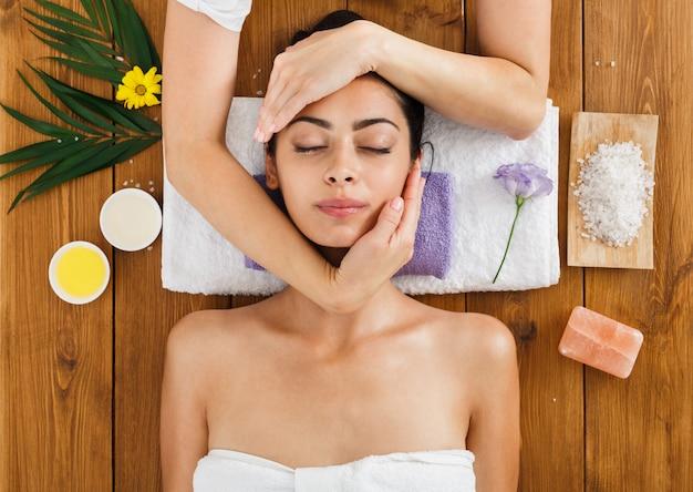 Woman massagist make face lifting massage in spa wellness center