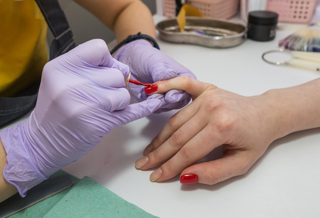 A woman master paints nails with red varnish for a client in a manicure in the salon. nail care concept.