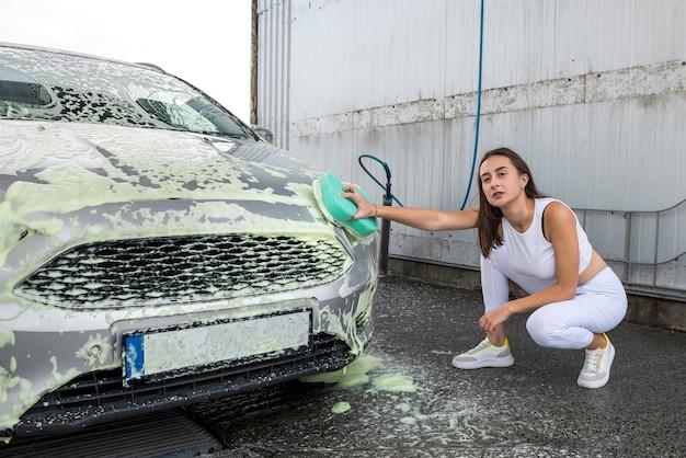 흰색 거품에 녹색 스폰지를 사용하여 자동차를 흙에서 청소하는 여성 마스터