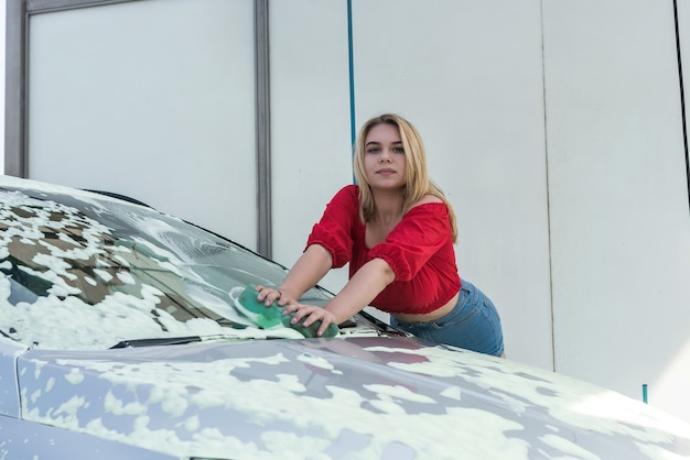 Woman master using green sponge in white foam to clean her auto from dirt