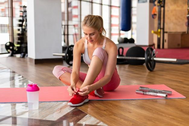 Woman on mat bind shoeslaces