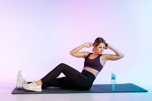 Woman on mat doing abdominal exercise