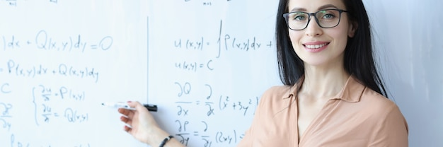 수식으로 칠판에 서서 열린 책을 들고 안경을 쓴 여성 수학자