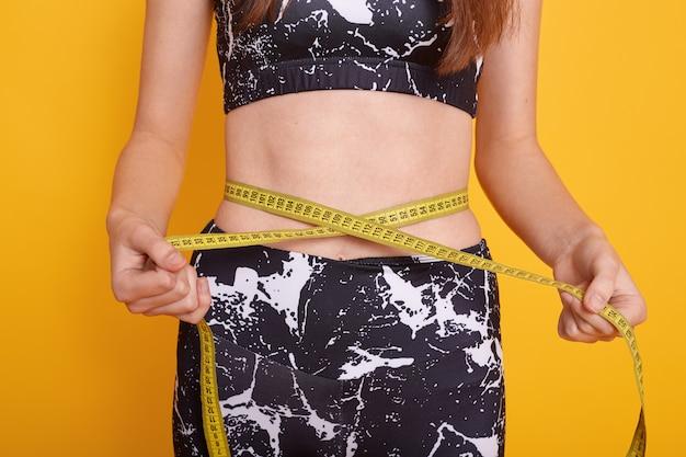 女性は黄色の壁に分離されたポーズスリムなモデルポーズメーター棒で彼女の腰腹を測定します。