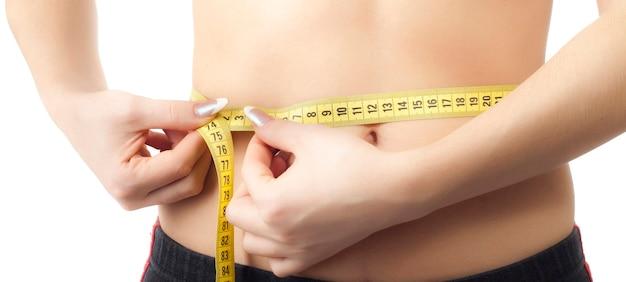 女性はメートルスティックで腰の腹を測定します