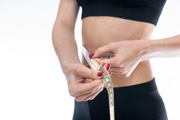 女性は白で隔離の巻尺でウエストを測定します