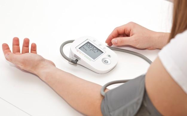 Woman measures blood pressure at home