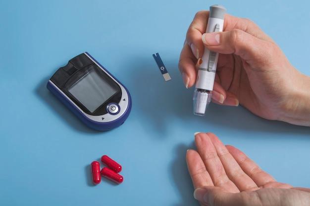 Женщина измеряет уровень сахара в крови с помощью глюкометра. концепция диабета на синем фоне