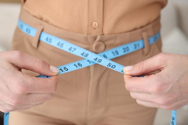 女性はセンチメートルのクローズアップで彼女の腰を測定します