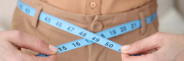 Woman measures her waist with centimeter closeup