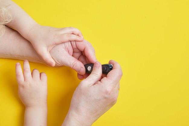 女性は女の子の血糖値を測定します