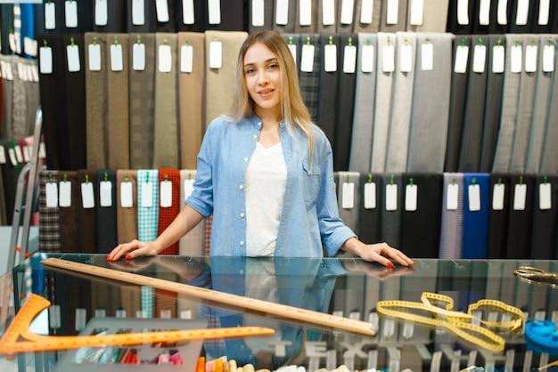 Женщина измеряет ткань в текстильном магазине. полка с тканью для шитья Premium Фотографии