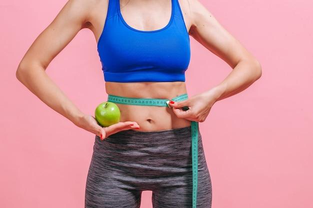 Женщина измеряет талию и показывает зеленое яблоко на розовой стене