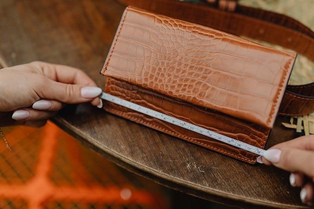 革の財布を測定する女性