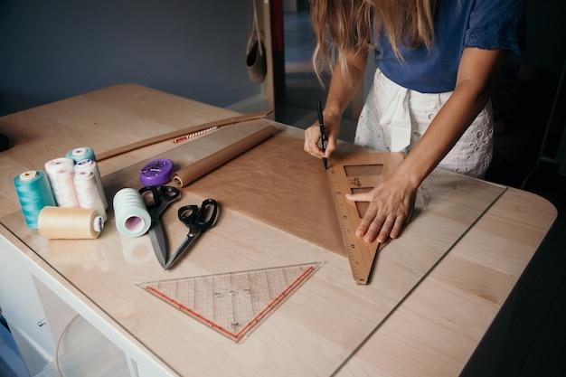女性は布のパターンを測定します。コンセプトを調整します。縫製事業コンセプト
