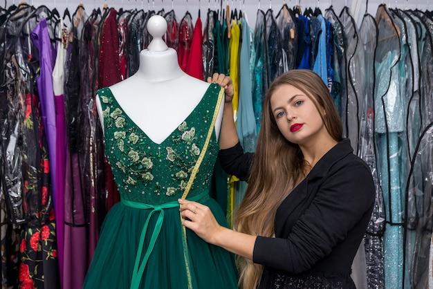 미터와 아름 다운 이브닝 드레스를 측정하는 여자