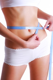 Woman measuring beauty slim waist. health eating concept