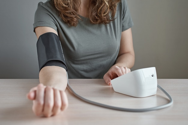 Woman measuring blood pressure herself with digital pressure gauge. health care and medical concept