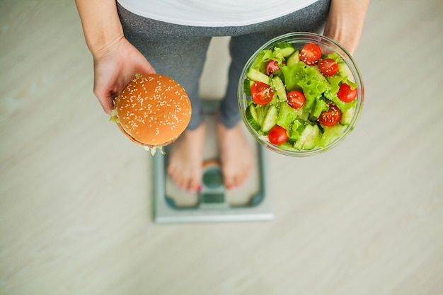 Woman measuring body weight on weighing scale holding burger and salad, sweets are unhealthy junk food, dieting, healthy eating, lifestyle, weight loss, obesity, top view
