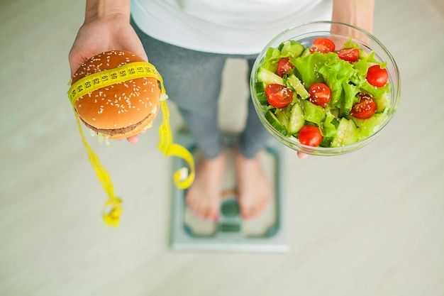 Woman measuring body weight on weighing scale holding burger and salad.