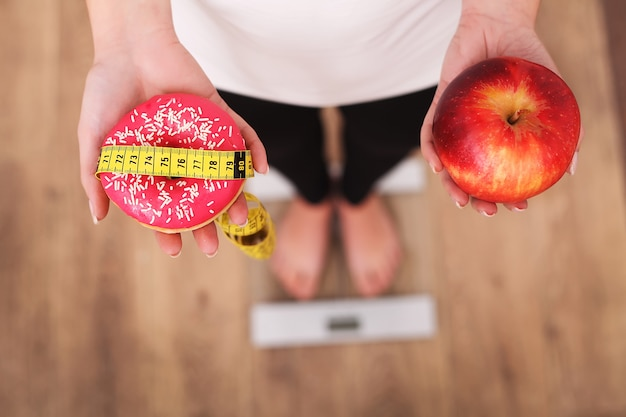 Woman measuring body weight on weighing scale holding donut and apple.