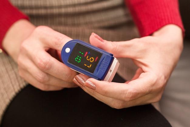 自宅のソファに座って血中酸素濃度を測定している女性