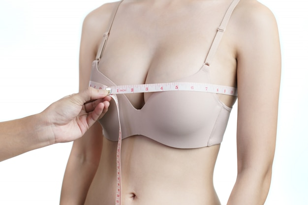 Woman measuring her chest for breast implant surgery.