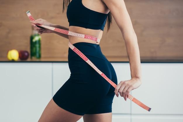 Женщина, измеряющая ее талию. идеальное стройное тело