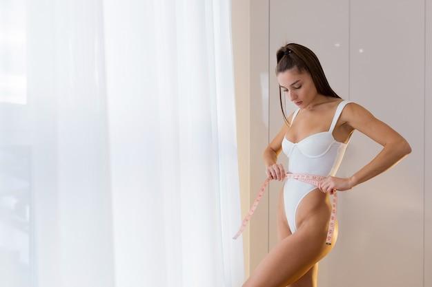 그녀의 허리 둘레를 측정하는 여자. 완벽한 슬림 바디