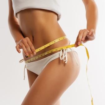 Woman measuring her waistline . perfect slim body