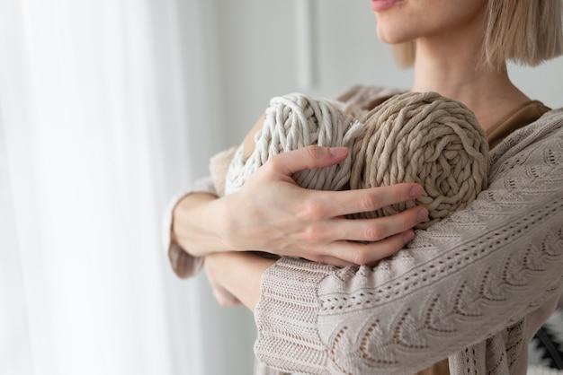 Женщина меряет кусок веревки из катушки для плетения макраме большими портновскими ножницами