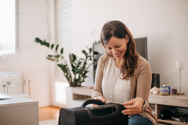 Woman measuring suitcase before going on holiday.