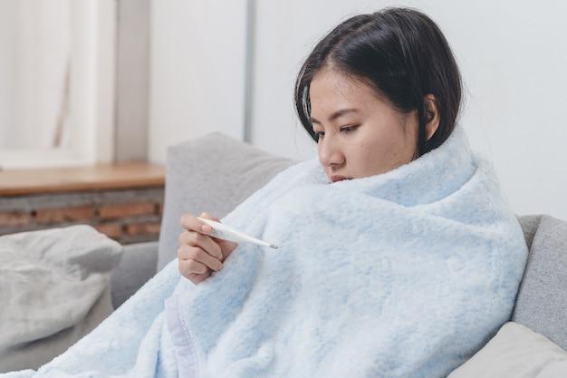 女性はベッドの上の彼女の体の温度を測定します。人はソファーに横になって発熱しました。