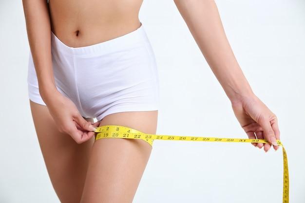 측정 테이프를 가진 허벅지와 다리 크기를 측정하는 여자