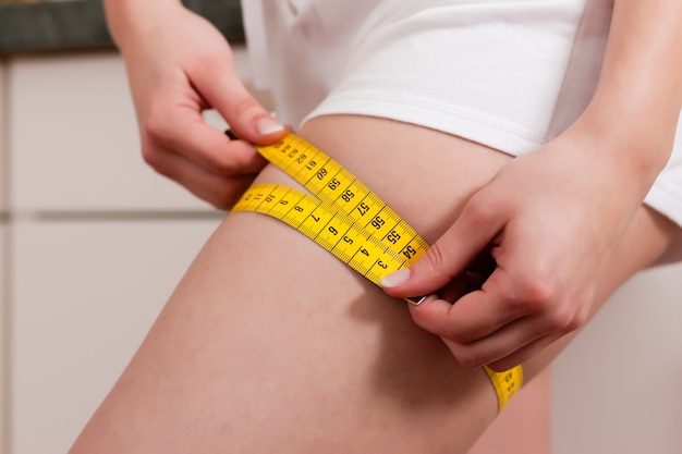 테이프와 허벅지를 측정하는 여자