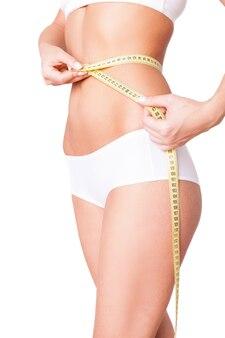 Женщина измерения тонированную талию. обрезанное изображение женщины в белом бюстгальтере и трусиках, измеряющей ее талию, стоя изолированной на белом