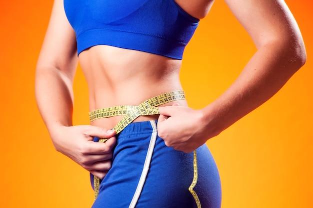 女性の腰を測定します。ダイエットとフィットネスの概念