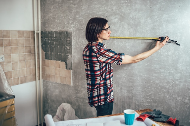 Woman measuring wall in kitchen