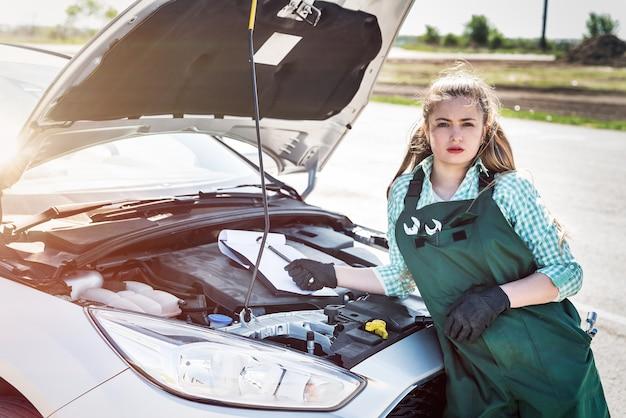 クリップボードで車のエンジンを調べる女性整備士
